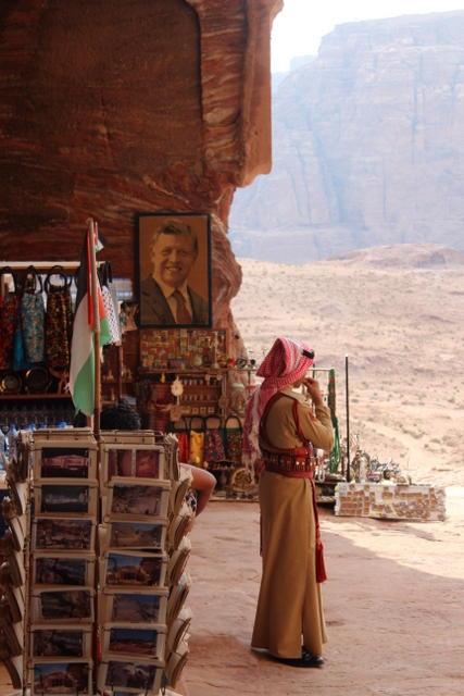 King Abdullah's portrait, flag, traditional dress. Jordan in a single image.